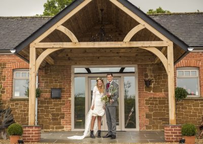 Bride and Groom standing at Ash Tree Barns front entrance. The bride has slightly pulled up her dress to reveal that she is wearing black Dr Marten boots