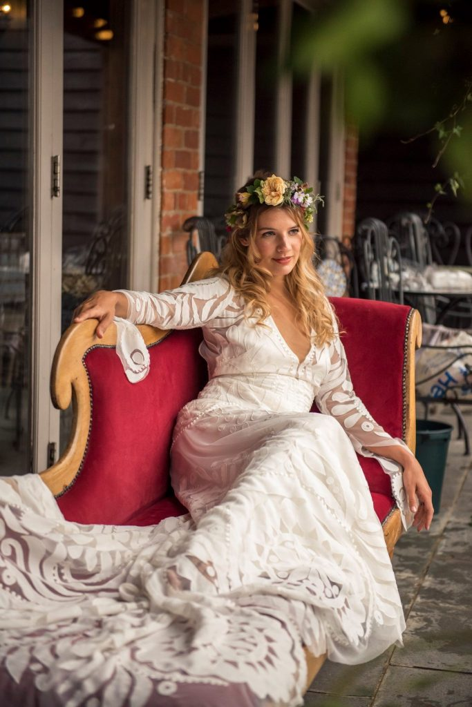 Beautiful bride in a gorgeous wedding dress with long blonde hair and floral crown, stretched out on a chaise.
